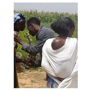 äthiopische Frau mit Baby auf dem Rücken, im Hintergrund begrüßen sich eine Frau und ein Mann