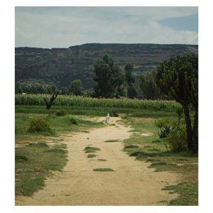 Landschaft Äthiopiens, in der Ferne läuft eine Frau